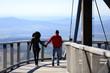 Para młodych ludzi spaceruje trzymając się za ręce po platformie widokowej nad górami.
