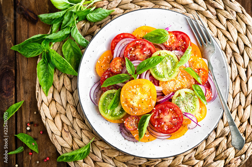 Foto Murales Tomato salad. Fresh vegetable salad with tomatoes, onion and basil