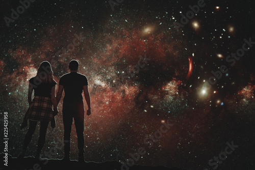 The silhouette of a lovers pair who looks at the night sky. A conceptual illustration of the silhouettes of people watching the cosmos. Boy and girl holding hands looking at the stars.