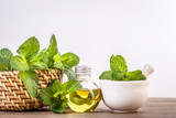 Aroma essential oil from a peppermint in the bottle on the table with fresh green mint leaf - 225437759