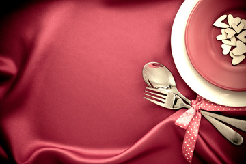 red heart shape with White empty plate with fork and spoon on red silk fabric for love dinner concept © pinkomelet