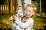 Little dog with happy owner spend a day at the park playing and having fun.Funny photo of laughing girl,she hugging and playing with beautiful Dalmatian puppy. Positive emotions of children fun games