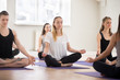 Leinwanddruck Bild - Group of young sporty people practicing yoga lesson with instructor, doing Sukhasana exercise, Easy Seat pose, working out, indoor, students training in club, studio close up. Well-being concept
