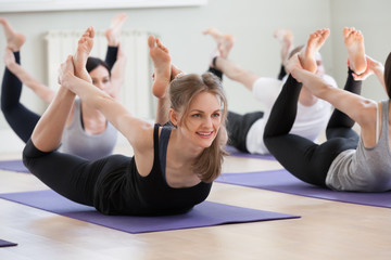 Group of young sporty people practicing yoga lesson, smiling woman doing Dhanurasana exercise, Bow pose, working out, indoor, students training in club, studio full length. Well-being concept