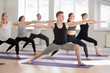 Leinwanddruck Bild - Group of young attractive sporty people practicing yoga lesson, doing Warrior Two exercise, Virabhadrasana II pose, working out indoor full length, students training in club studio. Well-being concept