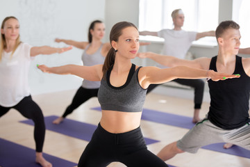 Attractive yogi woman and a group of young sporty people practicing yoga lesson, doing Warrior Two exercise, Virabhadrasana II pose, working out indoor, students training in studio. Well-being concept