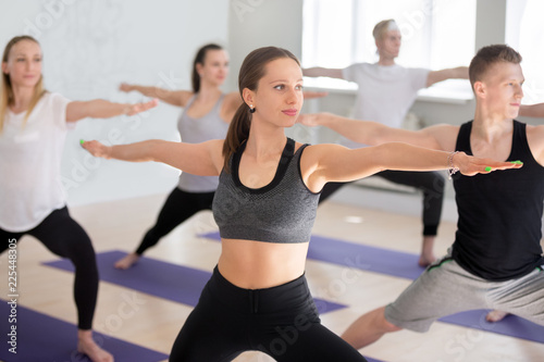 Leinwandbild Motiv Attractive yogi woman and a group of young sporty people practicing yoga lesson, doing Warrior Two exercise, Virabhadrasana II pose, working out indoor, students training in studio. Well-being concept