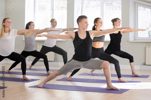 Leinwandbild Motiv Group of young attractive sporty people practicing yoga lesson, doing Warrior Two exercise, Virabhadrasana II pose, working out indoor full length, students training in club studio. Well-being concept