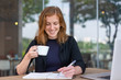 Positive student reading copybook during coffee break. Young woman in dark blue jacket drinking coffee and writing notes in notebook. Studying anywhere concept