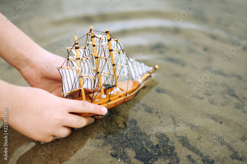 Fototapeta child playing with a toy sailing ship by the river, hand closeup