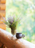 Clay cup with coffee and  bouquet of  heathers on the railing of the balcony. Selective focus. Shallow depth of field. - 225456149