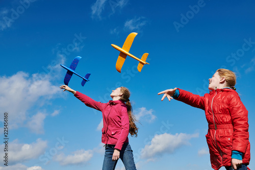 Foto Murales Girls playing with airplane at blue sky. Tand and childhood vacation concept