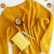 Yellow bright sweater with notepad, pen, glasses and a cup of coffee. Autumn mood and style. Top view, flat lay