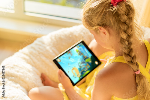 Leinwandbild Motiv Girl playing game on tablet computer