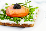 Canape with smoked salmon, soft cheese, tomato and caviar. Symbolic image. Concept for a tasty and healthy meal. Food background. White background. Close up.  - 225458980