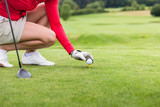 Close-up of female golf player placing golf ball on tee at green