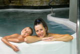 Happy mother and daughter relaxing in a thermal pool - 225463771
