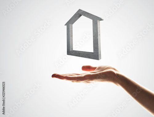 Real estate or mortgage concept by house symbol on hand. Mixed media - 225466323