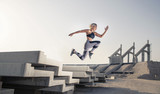 Middle Eastern Girl with short braided hair jumping of a stack of blocks on a  construction site wearing gray and black fitness outfit on a hot bright sunny day.