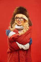 Portrait of charming blond woman in winter white sweater, hat with earflaps, wearing mittens and covered blanket, standing on red isolated background. © Ilshat