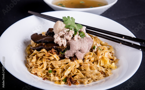 Traditional spicy dry noodles served with mushrooms and pork. Bak Chor Mee from Singapore. - 225474528