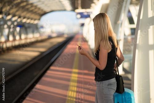 Fototapeta Woman waiting for train on train station platform
