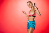 attractive smiling sportswoman listening music with smartphone and dancing isolated on red