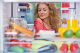 Woman standing in front of fridge full of groceries and looking something to eat. Picture taken from the inside of fridge. - 225490378