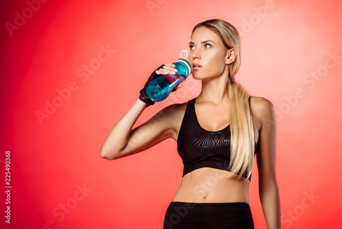 Foto Murales attractive sportswoman drinking water from sport bottle isolated on red