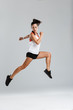 Young sports woman jumping make sport exercises isolated indoors.
