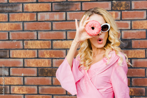 Foto Murales surprised young woman in pink shirt looking at camera through donut in front of brick wall