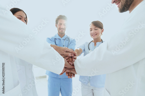 Leinwanddruck Bild Doctors and nurses in a medical team stacking hands