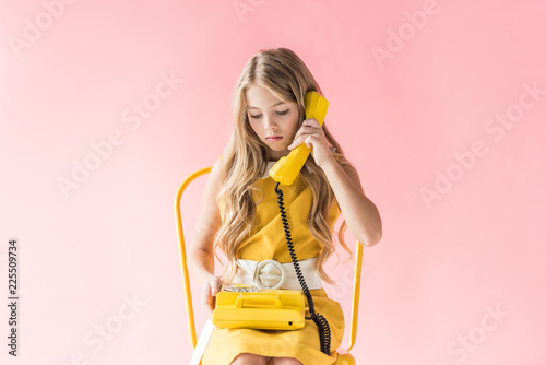 Foto Murales stylish blonde preteen child talking on retro telephone while sitting on yellow chair on pink