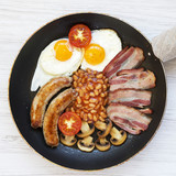Full English Breakfast in cooking pan with sausages, fried eggs, beans and bacon on a white wooden background, overhead view. Flat lay, from above, top view. - 225509989
