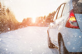 White car on a winter road through a snow covered forest.  - 225513577