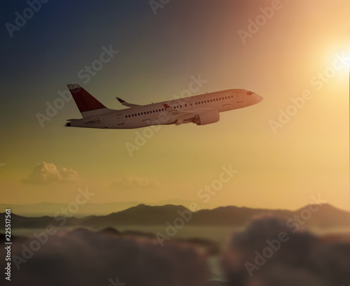 Airplane during flight over clouds before sunset