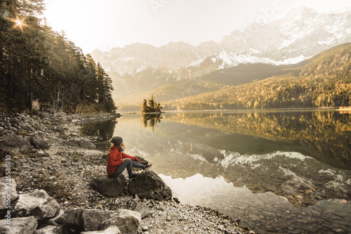 A young blond girl sit on peak and enjoy sun. Woman hiker watch sunrise. Impressive Autumn landscape The Eibsee Lake in front of the Zugspitze under sunlight. Amazing sunny day