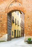 Street through a city gate to an old Italian village