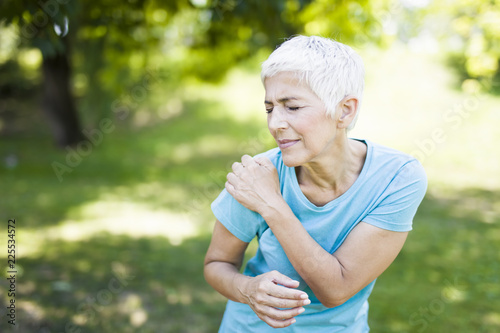 Senior sporty woman has shoulder pain in the park - 225534572