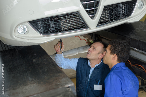mechanics checking the technical state underneath a car