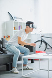 emotional young asian man using virtual reality headset at home - 225541113