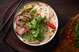 Vietnamese traditional soup Pho Bo with beef and fresh coriander on dark wooden background - 225545595