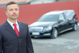 Portrait of funeral director standing in front of hearse - 225553185