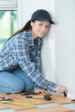 female floor installer inserting the wedges - 225560349