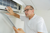man using a tablet to adjust air conditioning system