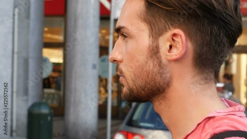 Attractive young man walking in the middle of city street looking at camera, crossing in front of cars