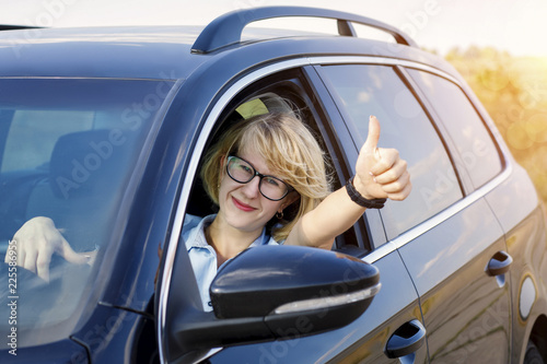 Fototapeta Woman in the car shows the hand gesture .