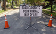 Humorous humourous construction barricade on neighborhood neighbourhood street flanked with orange safety cones.
