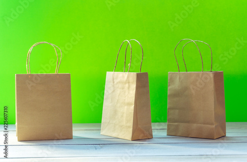 Ecological paper bags against green background - 225607310