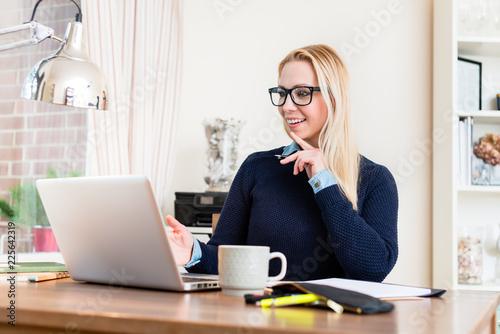 Leinwandbild Motiv Portrait of smiling woman at her desk looking at laptop